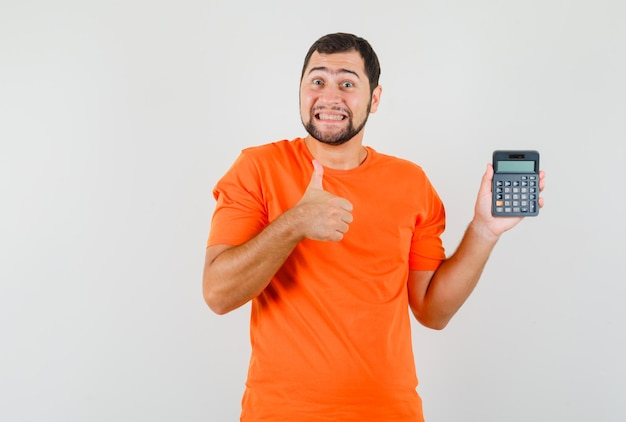 주황색 티셔츠를 입은 젊은 남성이 엄지손가락을 위로 들고 계산기를 들고 쾌활하고 앞모습을 보고 있습니다.