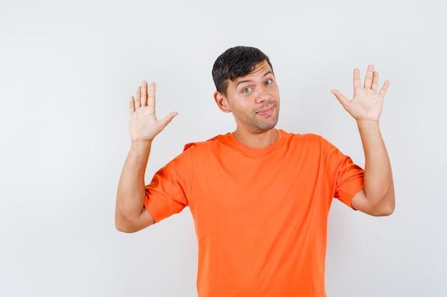 항복 제스처에 손바닥을 제기하고 용감한 찾고 주황색 티셔츠에 젊은 남성