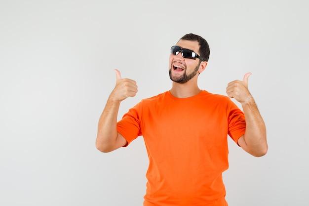 주황색 티셔츠를 입은 젊은 남성이 엄지손가락을 두 번 위로 올리고 쾌활하고 앞모습을 보고 있습니다.