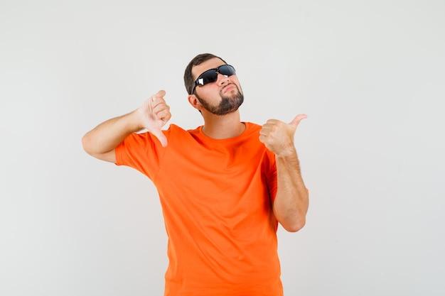 Молодой мужчина в оранжевой футболке показывает большие пальцы руки вверх и вниз и выглядит смущенным, вид спереди.