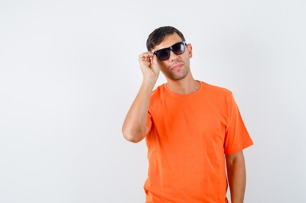 オレンジ色のtシャツを着た若い男性が眼鏡に触れてかっこよく見えます