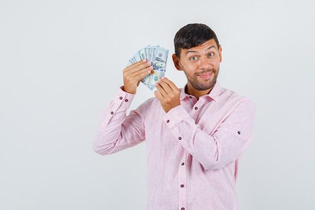 Молодой мужчина в розовой рубашке держит долларовые купюры и выглядит веселым, вид спереди.