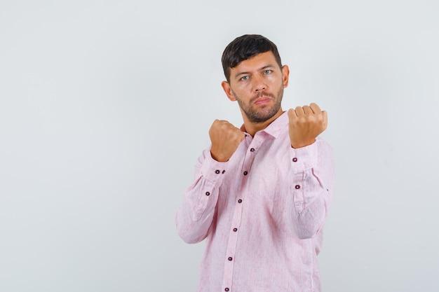 Молодой мужчина в розовой рубашке держит кулаки в позе боксера и выглядит сильным, вид спереди.