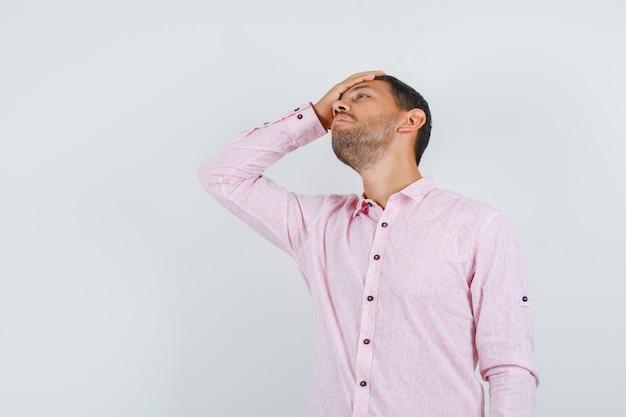 額に手を握って混乱しているように見えるピンクのシャツを着た若い男性、正面図。