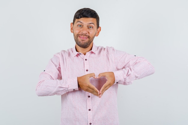 Молодой мужчина в розовой рубашке делает форму сердца руками и выглядит веселым, вид спереди.