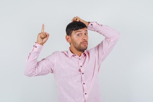ピンクのシャツを着た若い男性が頭を掻いて上向き、正面図。