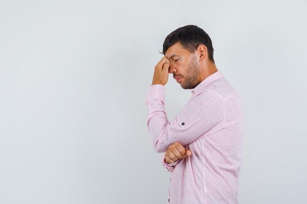 Молодой мужчина в розовой рубашке думает с закрытыми глазами.