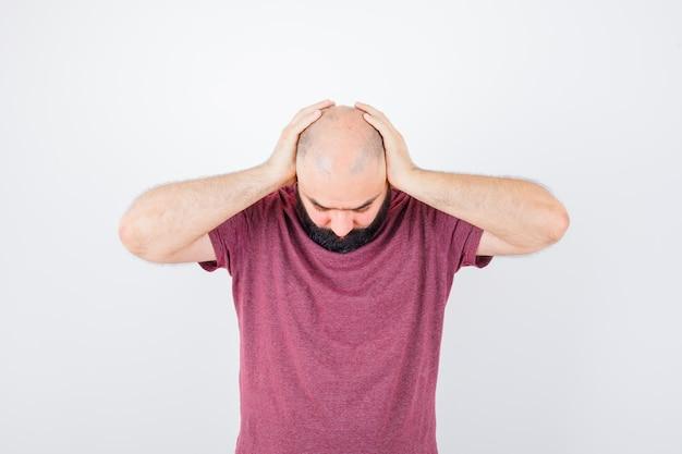 ピンクのtシャツを着た若い男性が見下ろし、ストレスの多い正面図を見て頭に手をつないでいます。