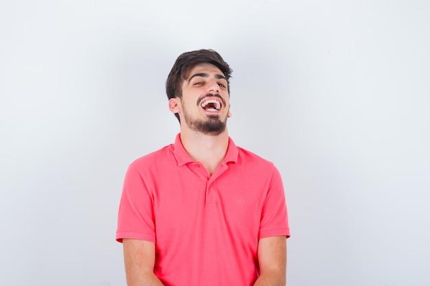 Молодой мужчина в розовой футболке смеется и выглядит уверенно, вид спереди.