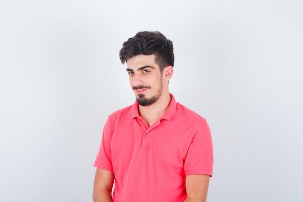 ピンクのtシャツを着た若い男性が見た目も賢明な見た目、正面図。