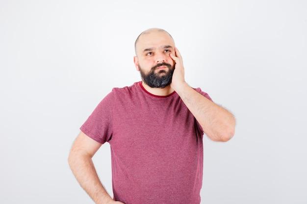 ピンクのtシャツを着た若い男性が顔に手を握り、物思いにふける、正面図を見て目をそらします。