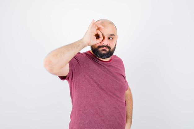Молодой мужчина в розовой футболке делает круг на его глазах, вид спереди.