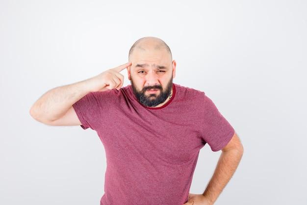 Молодой мужчина в розовой футболке, указывая на его висок, вид спереди.