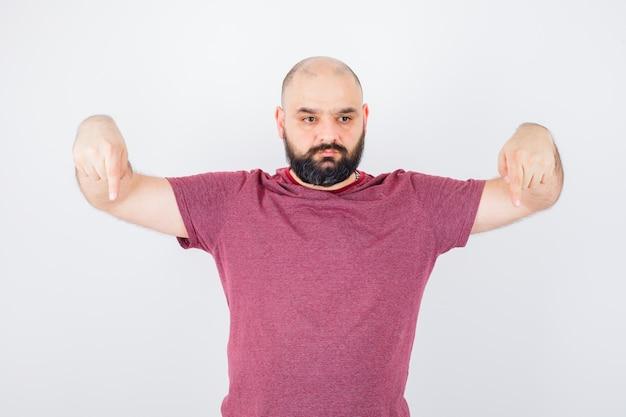 下向きのピンクのtシャツの若い男性、正面図。