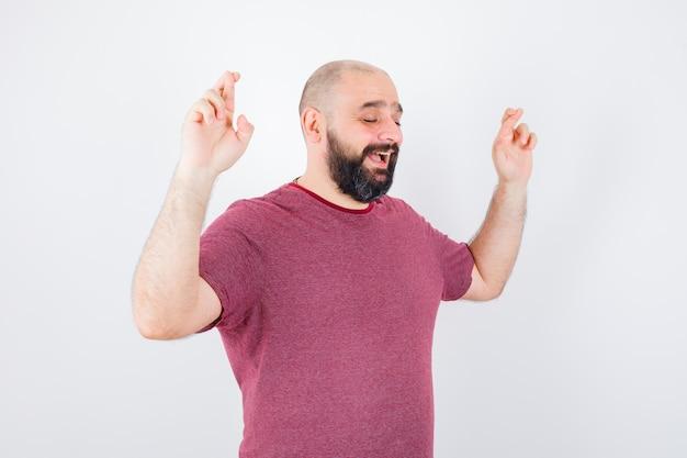 분홍색 티셔츠를 입은 젊은 남성이 웃고 있는 동안 손가락을 교차시킵니다.