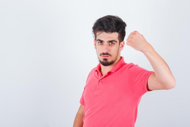 くいしばられた握りこぶしを示し、自信を持って見えるピンクのtシャツの若い男性、正面図。