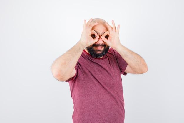 Молодой мужчина в розовой футболке показывает жест в очках и выглядит смешно, вид спереди.