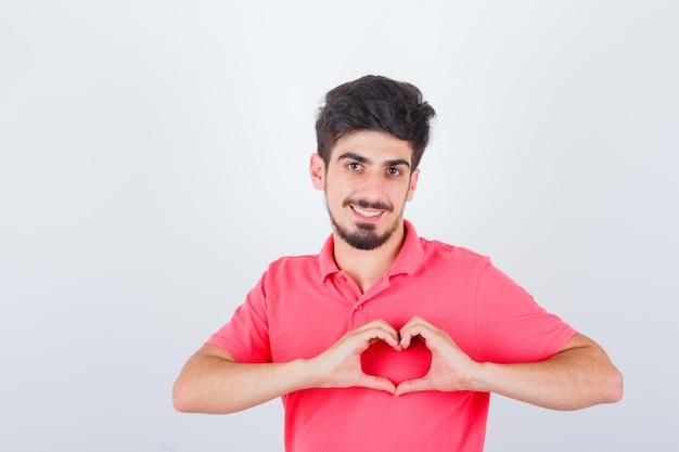 ピンクのtシャツを着た若い男性は、心臓のジェスチャーを示し、自信を持って、正面図を表示します。