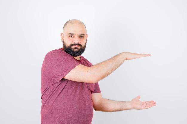 Молодой мужчина в розовой футболке показывает знак среднего размера и выглядит уверенно.