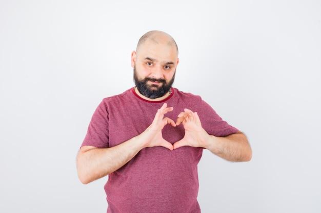 Молодой мужчина в розовой футболке, показывая жест мира и глядя на любимого, вид спереди.