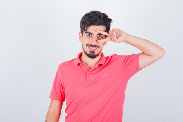 Молодой мужчина в розовой футболке показывает v-знак на глазах и выглядит веселым, вид спереди.