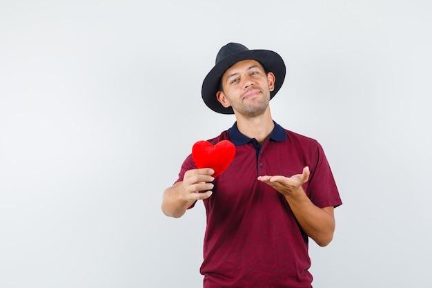 赤いシャツを着た若い男性、赤いハートを示し、リラックスして見える黒い帽子、正面図。