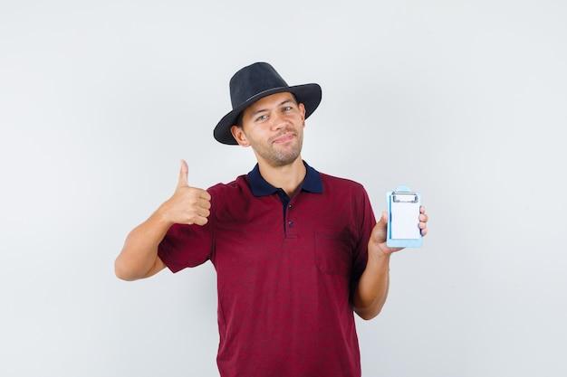 赤いシャツを着た若い男性、小さなノートを持って感謝している間、親指を上に表示している黒い帽子、正面図。