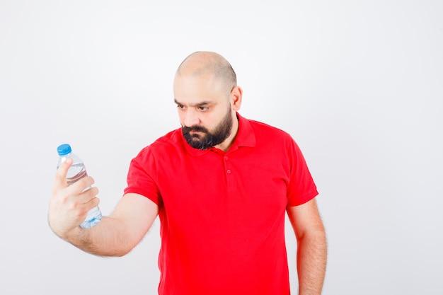 赤いシャツを着た若い男性がボトルを見て、注意深く見て、正面図。