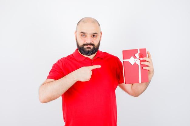 현재 상자, 전면 보기를 가리키는 빨간 셔츠에 젊은 남성.