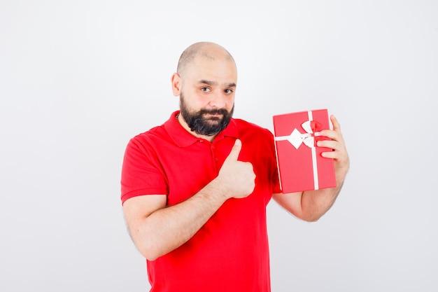 엄지손가락을 보여주는 동안 선물 상자를 보여주는 빨간 셔츠에 젊은 남성, 전면 보기.