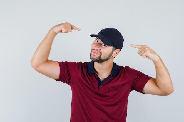 赤いtシャツを着た若い男性、彼の帽子を指して、かわいく見える黒い帽子、正面図。