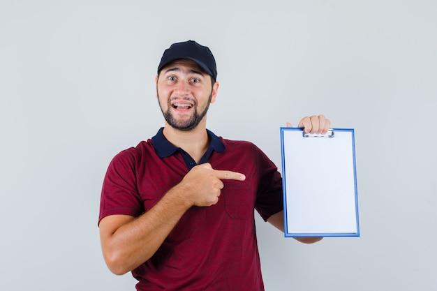 赤いtシャツを着た若い男性、彼のノートを指して喜んでいる黒い帽子、正面図。