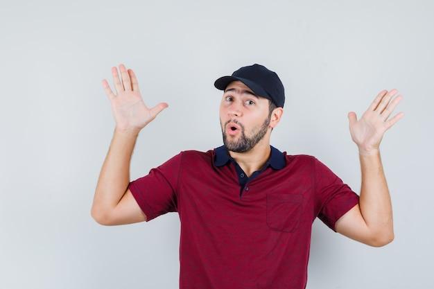 Молодой мужчина в красной футболке, черной кепке демонстрирует беспомощный жест и выглядит потрясенным, вид спереди.