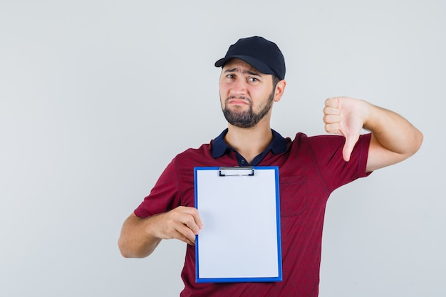 赤いtシャツを着た若い男性、ノートブックを持って悲しそうに見える間、親指を下に見せている黒い帽子、正面図。