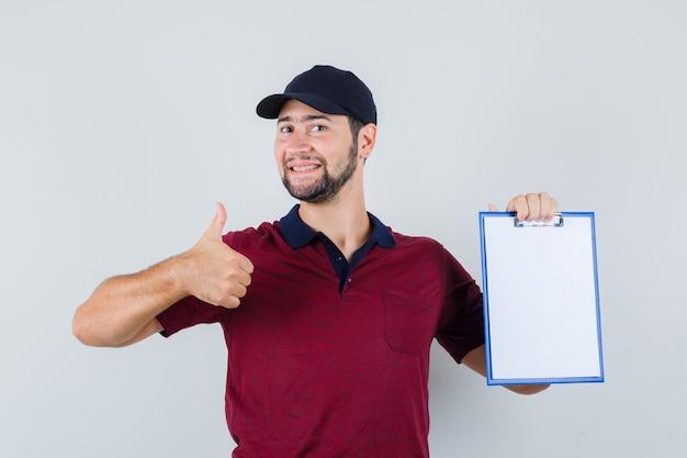 赤いtシャツを着た若い男性、ノートブックを持って嬉しそうに見ながら親指を立てて黒い帽子、正面図。