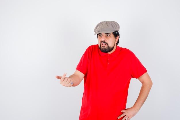 赤いtシャツを着た若い男性、手のジェスチャーで誰かを呼び出すキャップ、正面図。