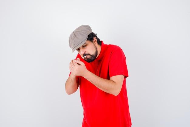 赤いtシャツ、キャップ喫煙、正面図の若い男性。 無料写真