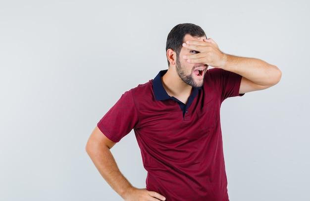 赤いtシャツを着た若い男性が、指で顔を覆い、面白く見えながら、正面から顔を覆っています。