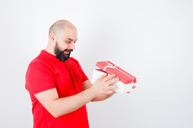 赤いtシャツを着た若い男性がギフトボックスを覗き込んで驚いて見える正面図。