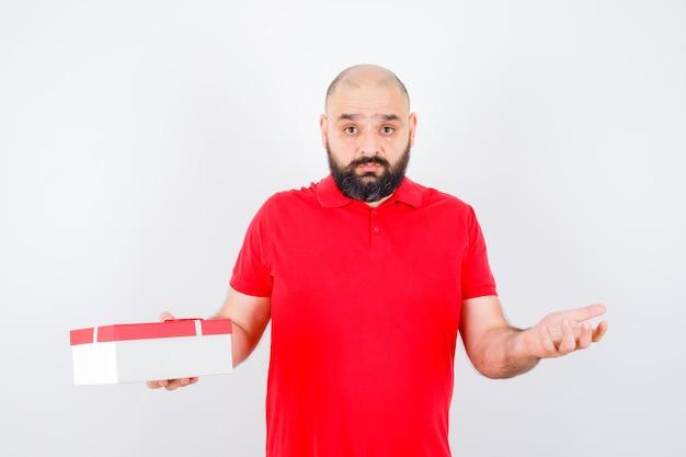 빨간 티셔츠를 입은 젊은 남성은 무력한 몸짓을 보여주고 절망적인 정면을 바라보고 있습니다.