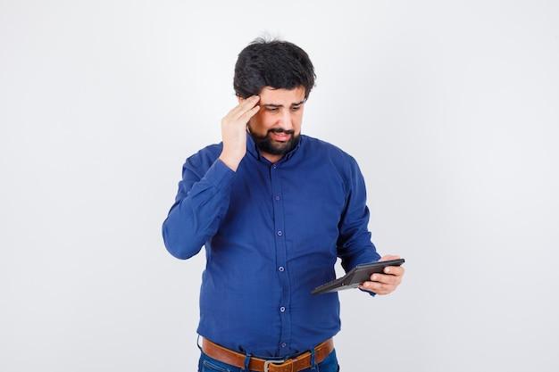 ロイヤルブルーのシャツを着た若い男性が計算して問題を抱えているように見える、正面図。