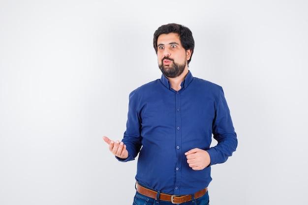Молодой мужчина в королевской синей рубашке что-то обсуждает и выглядит нервным, вид спереди.