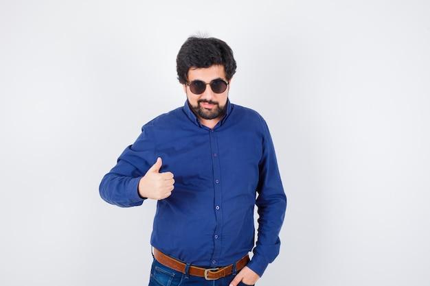 Молодой мужчина в королевской синей рубашке, очки показывает палец вверх и выглядит круто, вид спереди.