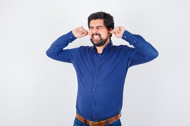 ロイヤルブルーのシャツを着た若い男性が指で耳を塞ぎ、ストレスの多い正面図を探しています。