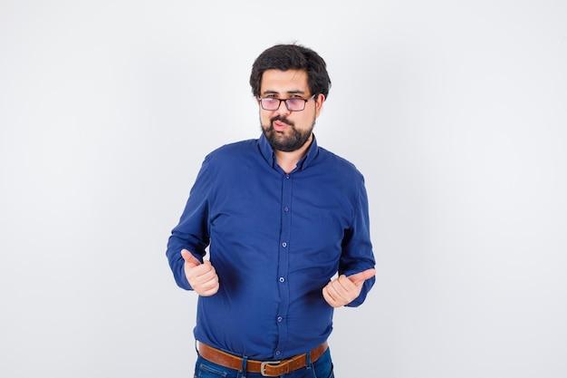 ロイヤルブルーのシャツを着た若い男性、親指を立てて、唇をふくれっ面を見せて、うれしそうに見える、正面図。