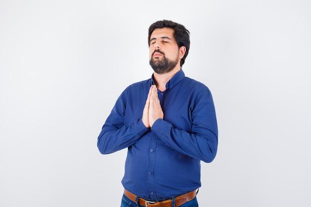 希望と希望を持って見えるロイヤルブルーのシャツを着た若い男性、正面図。