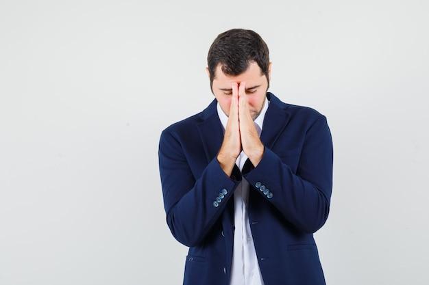 シャツとジャケットの若い男性は、祈りのジェスチャーで手をつないで、希望を持って見えます