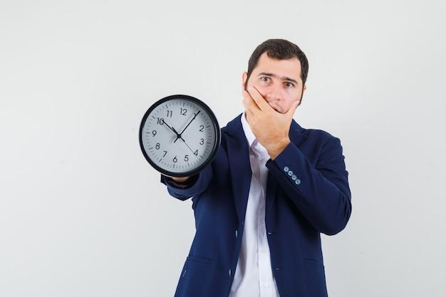 Молодой мужчина в рубашке и куртке показывает настенные часы и выглядит беспомощным