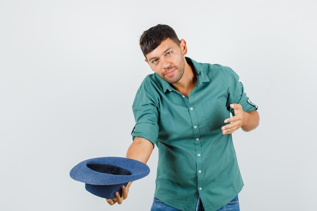 셔츠를 숙이고 모자를 벗고 쾌활한 찾고있는 젊은 남성