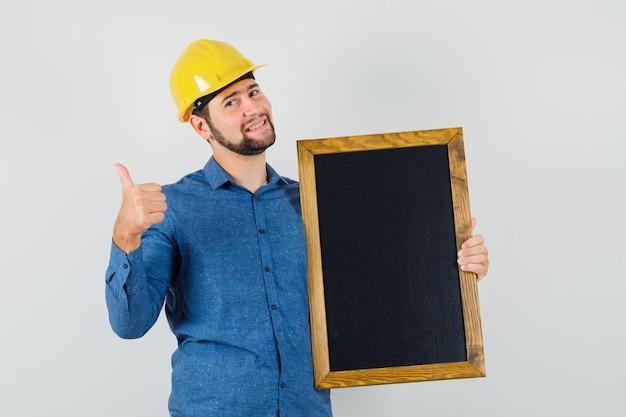 젊은 남성 셔츠, 헬멧 칠판을 들고 엄지 손가락을 표시 하 고 쾌활 한, 전면보기를 찾고.